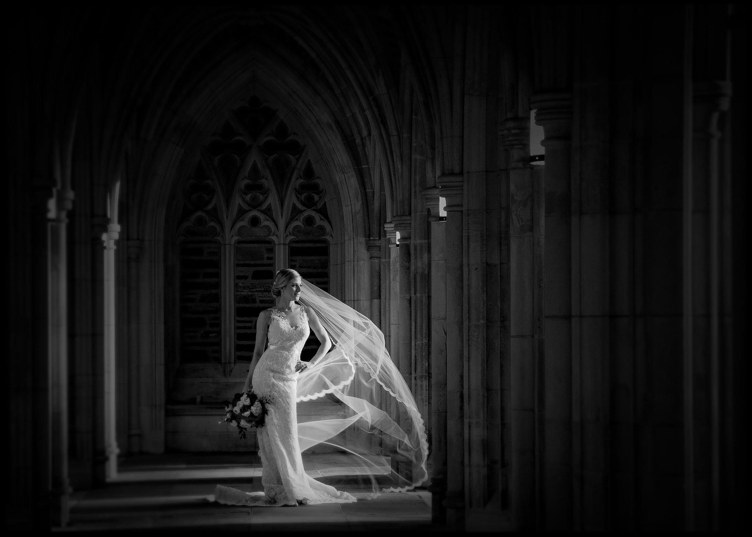 Duke Chapel Wedding Photo - B&W Bridal Portrait in Arcades with Billowing Veil