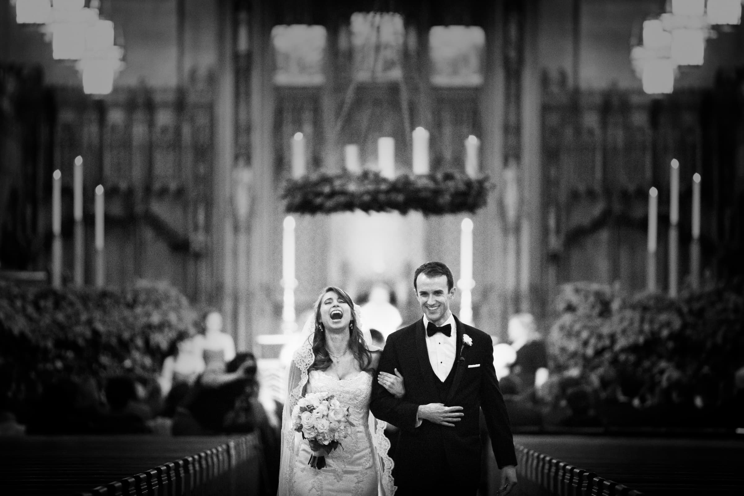 Duke Chapel Wedding Photographer - B&W couple laughing during recessional