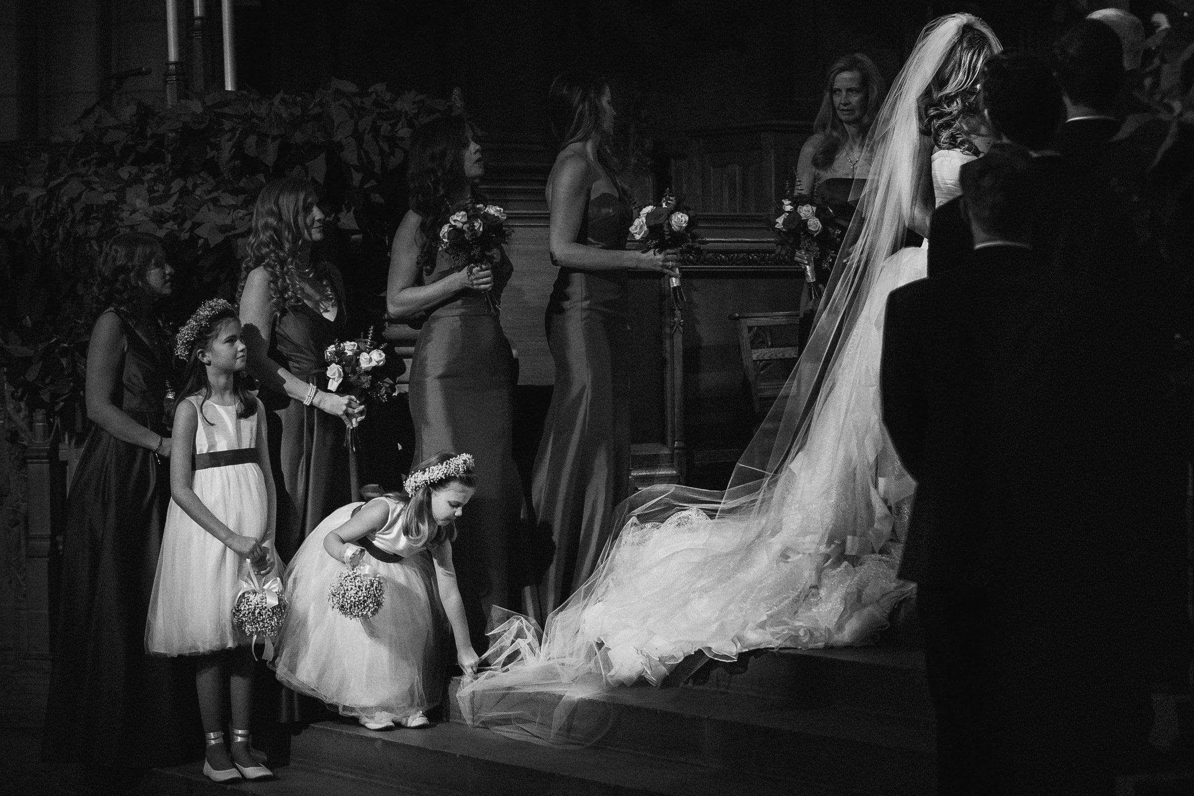 B&W Duke Chapel Wedding Photo by Joe Payne of flower girl fixing dress