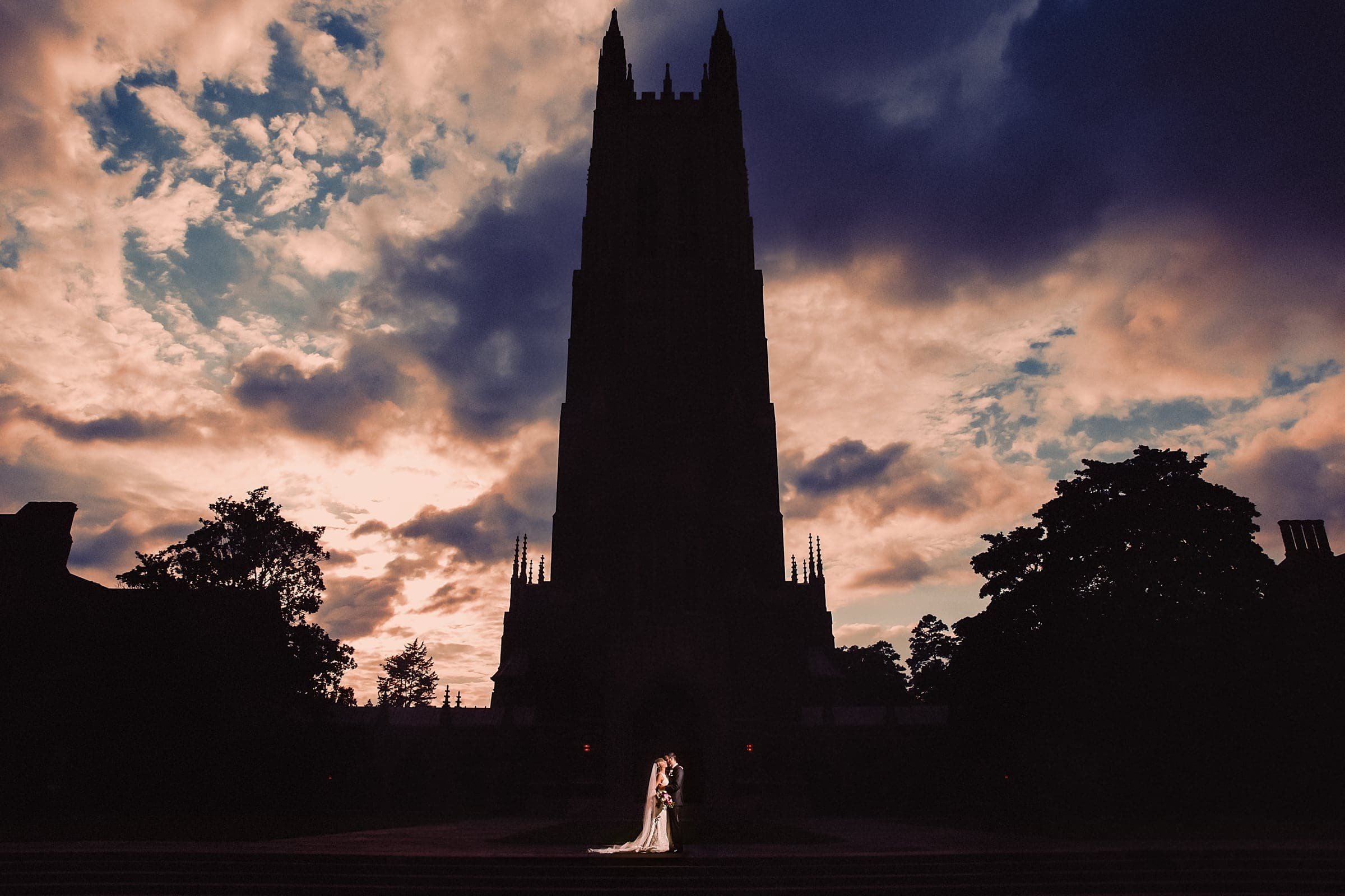 Duke Chapel Weddings - Couple in Silhouette of Chapel with Dramatic Sky