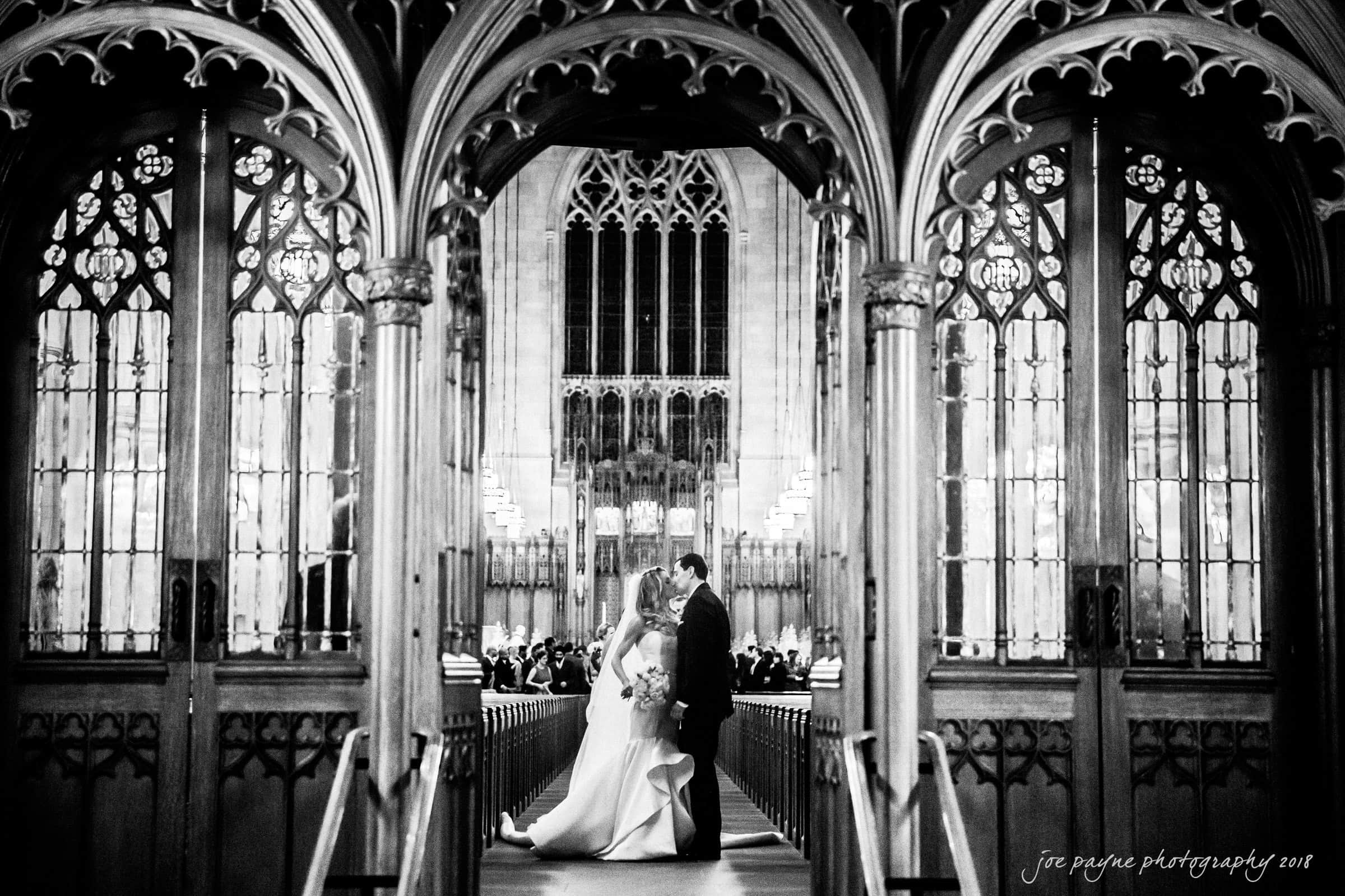 Duke Chapel Wedding Photo of Recessional Kiss Through Ornate Doors by Joe Payne in B&W