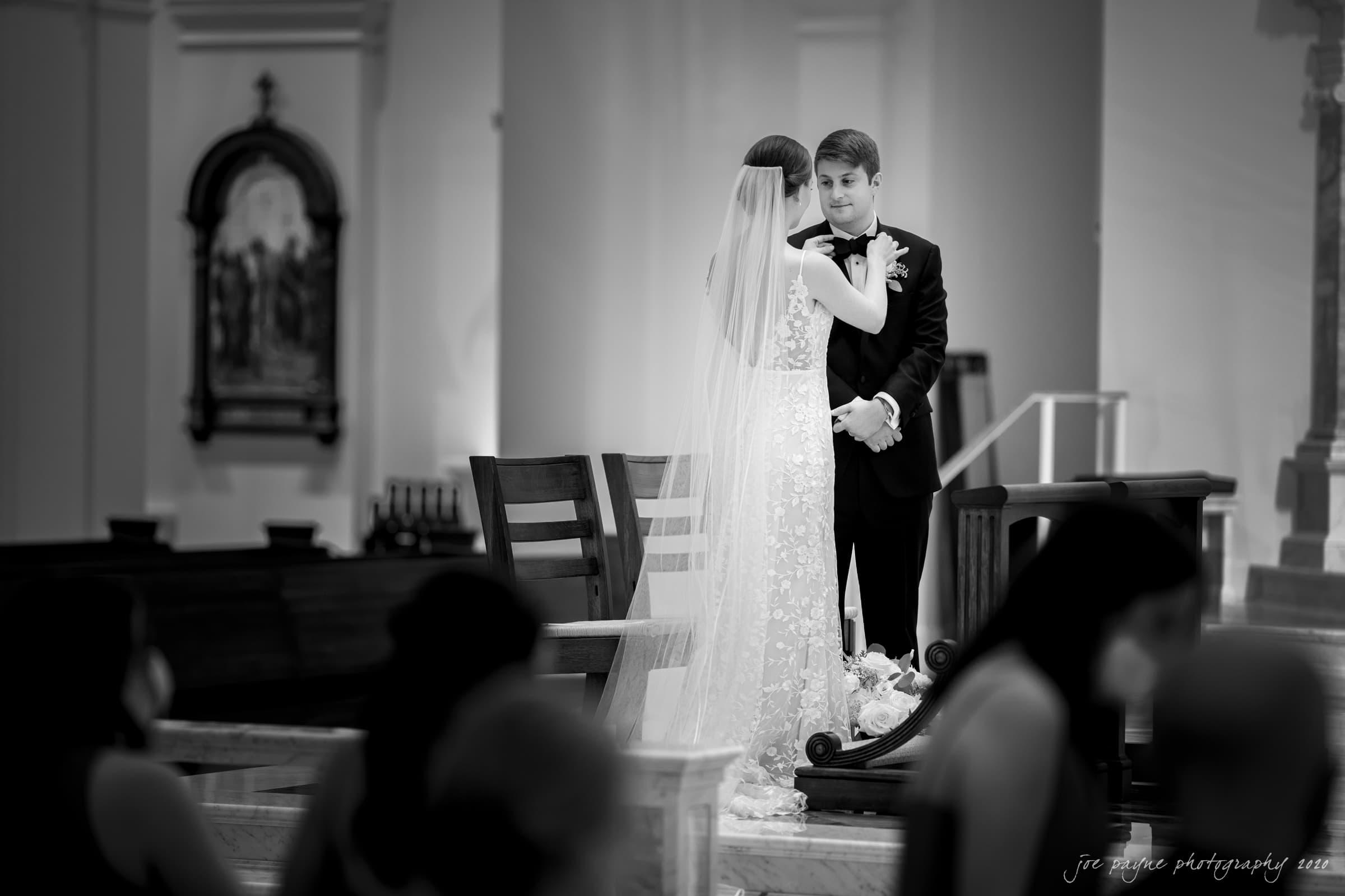 Holy Name of Jesus wedding bride fixes groom's bowtie