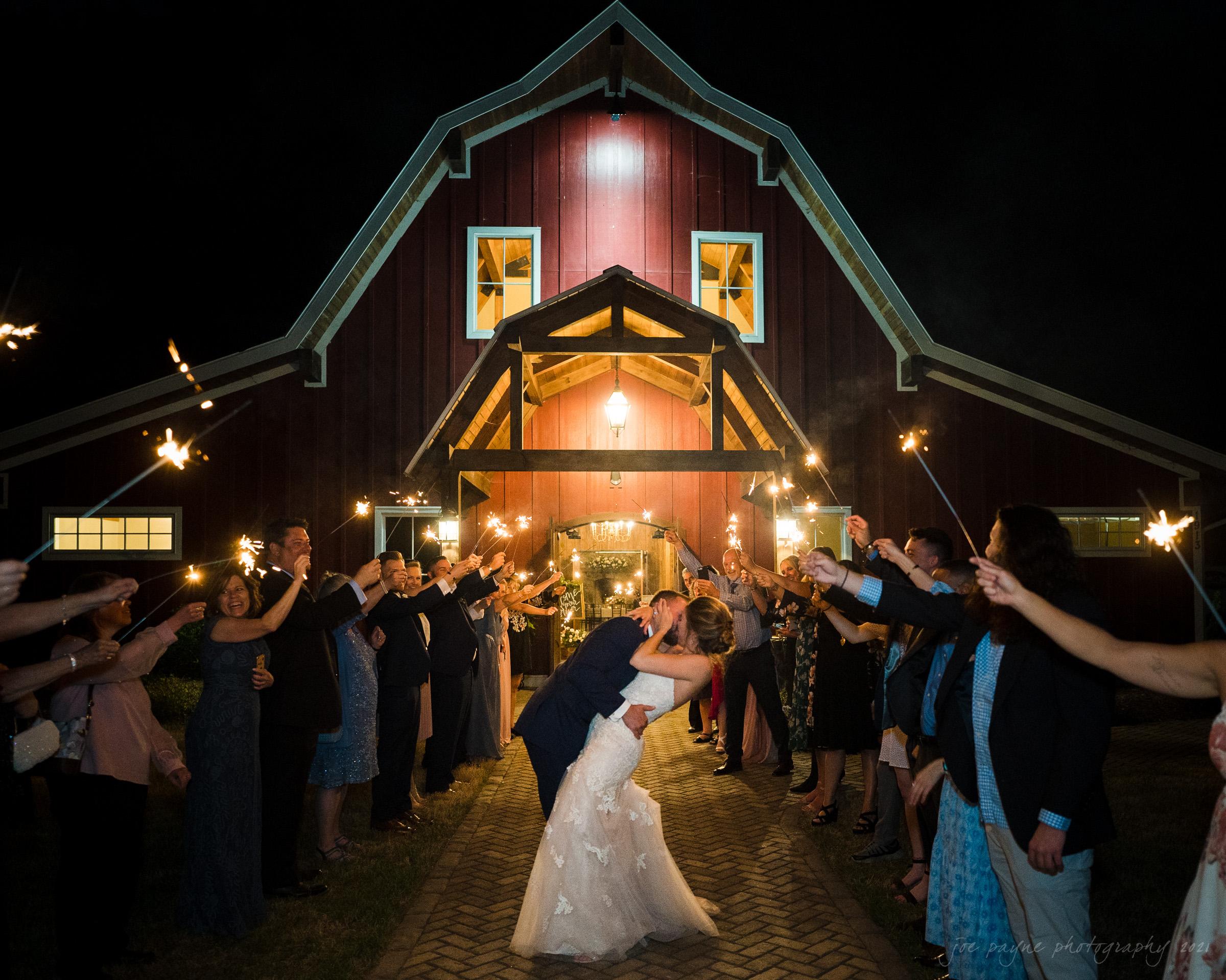 sacred heart church & pavilion at carriage farm wedding sparkler exit kiss